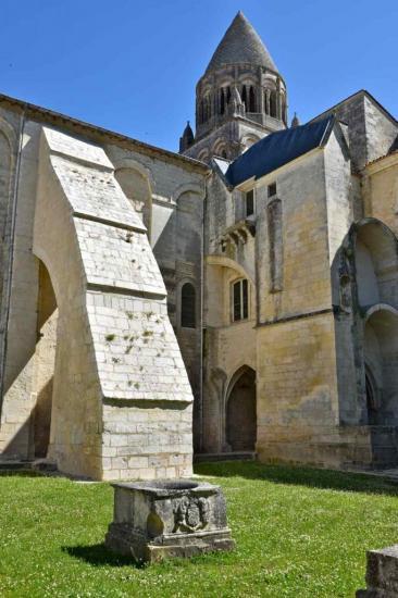 La margelle de l'ancien puits du cloître devant un énorme contrefort de l'église